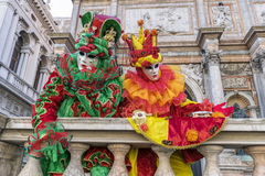 Venice Carnival Masks. A couple of multi coloured masks, posing for the photographers in San Marco square, Venice, Italy Stock Image