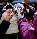 Venice Carnival Participant and Reveller Looking into Silver Ball. Venice Carnival participant picture amongst members of the general public and participating at Stock Photo