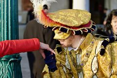Venice Carnival Participant and Reveller. Prince Charming Kissing hand. Venice Carnival Prince Charming kissing hand of stranger and posing for a picture amongst Stock Images