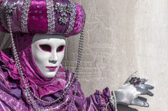 Venice Carnival purple Mask. A traditional mask posing near a column in Venice, Italy stock photography