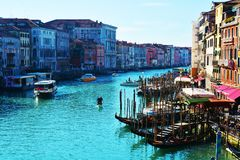 Venice in colorful hues. Beautiful Venetian cityscape from Ponte di Rialto bridge in colorful hues. Gondolas, boats and typical architecture stock photography
