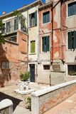 Venice court with ancient water well, buildings and houses in Italy. Venice court with ancient water well, buildings and houses facades in a sunny day in Italy royalty free stock photography