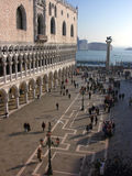 Venice: Doge's Palace by St Mark's Square. Early evening in Venice: Doge's Palace, Piazza San Marco, canal, lampposts and crowd of tourists, taken in early Royalty Free Stock Photos