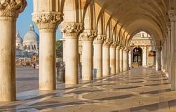 Venice - Exterior corridor of Doge palace. And church Santa Maria della Salute in background stock image
