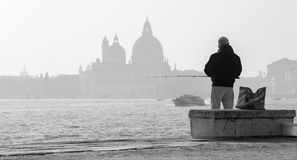 Venice - Fisherman from Riva S. Biagio waterfront and silhouette of Santa Maria della Salute church. Royalty Free Stock Photo