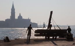 Venice - Fisherman from Riva S. Biagio waterfront and silhouette of Santa Maria della Salute church. Stock Photos
