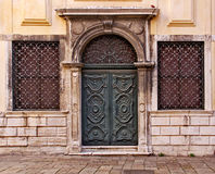 Venice, ghetto, wooden carved door. A wooden green decorated door flanked by two iron grated windows in the old Ghetto of Venice royalty free stock photos