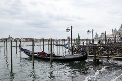 Venice gondola docked at Canale Grande. Single gondola docked at Canale Grande in Venice during cloudy day royalty free stock images