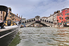 Venice Gondola Gr Canal Rialto Low. Grand canal of Venice towards Rialto bridge from approaching gondola to pass under historic landmark footbridge on tourist royalty free stock photos
