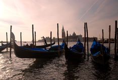 Venice - Gondola's. Gondola's silhouetted against the bright hazy morning sky, with San Giorgio Maggiore in the background and a Gondalier swishing by Stock Images