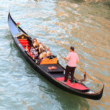 Venice gondola on water with people, from top. Venice gondola on water with people on-board and gondolier viewed from behind Royalty Free Stock Image