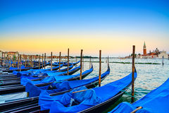 Venice, gondolas or gondole on sunset and church on background. Royalty Free Stock Photos