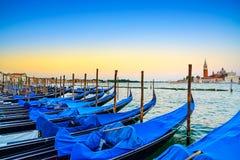 Venice, gondolas or gondole on sunset and church on background. Venice, gondolas or gondole on a blue sunset twilight and San Giorgio Maggiore church landmark royalty free stock photos