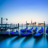 Venice, gondolas or gondole on sunset and church on background. Stock Photography