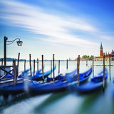 Venice, gondolas or gondole on sunset and church on background. Stock Photos