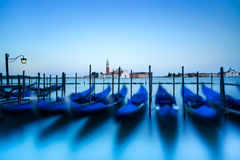 Venice, gondolas or gondole on sunset and church on background. Italy Stock Photos