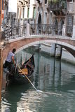 Venice Gondolier in a traditional venetian canal Royalty Free Stock Image
