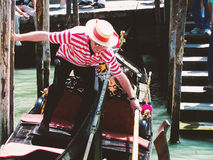 Venice gondolier trying to keep balance on the gondola boat. Taken in Venice in Italy during the summer Stock Image