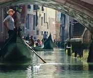 Venice gondolier. Venetian gondolier navigates the narrow canals and bridges between the buildings Stock Images