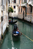 Venice Gondoliers. Two gondolas traveling down a canal street in Venice Royalty Free Stock Photos