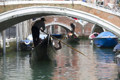 Venice gondoliers approaching a bridge Stock Image