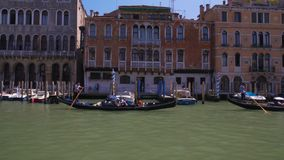 Venice gondoliers riding down Grand Canal, tourists traveling by boats, Italy. Stock footage stock video footage