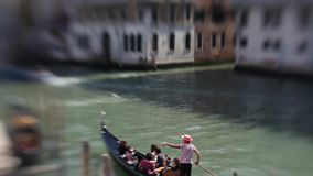 Venice, the Grand canal. A gondolier takes tourists on gondola. Tilt shift effect stock video