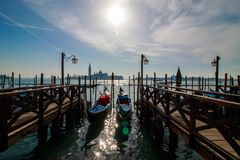 Venice italian city view with gondolas parked at seashore, channels and bridges, sea and clouds sky landscape at sunny day in Ital. Y, tourism and travelling stock image