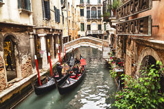 Venice, Italy – December 21, 2015: Tourists taking photo with gondolier in venetian canal in gondola. Venice. Italy. Venice, Italy – December 21, 2015 Royalty Free Stock Images