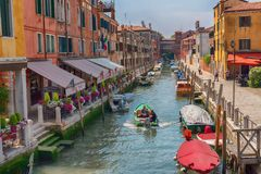 VENICE, ITALY – MAY 23, 2017: Traditional narrow canal street with gondolas and old houses in Venice, Italy. Royalty Free Stock Image