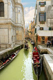 VENICE, ITALY- April 13, 2015: Beautiful city view and typical gondola at narrow venetian canal, Venice, Italy. Toned square image royalty free stock image