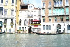 Beautiful gondolas with passengers are moving along the Grand canal in a sunny spring day. royalty free stock image
