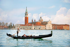 VENICE, ITALY - 13 APRIL 2015: Beautiful view of traditional Gondola on Canal Grande with San Giorgio Maggiore church in the backg Stock Photo