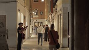 Lively alleyway with people walking among the stores. Venice, Italy. Venice, Italy - April 22, 2018: Evening view of people walking along alley with stores. Some stock footage