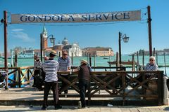 Gondoliers waiting at gondola service for customers at Saint Mark`s square in Venice. Venice, Italy - April 17 2019: Gondoliers waiting at gondola service for stock photos