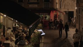 Lively street with outdoor cafe in night Venice, Italy stock footage