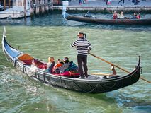 VENICE, ITALY - APRIL 29, 2017: Traditional gondola and tourists near Rialto bridge View in Venice Stock Photo