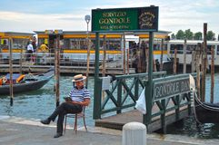 VENICE, ITALY - Aug 14, 2014: A gondolier is reading a book, Royalty Free Stock Photography