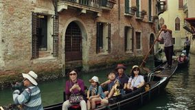 Venice, Italy - August 8, 2017. Asian family taking a ride on a famous Venetian gondola stock footage