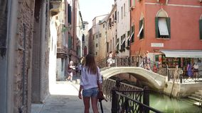 VENICE, ITALY - AUGUST 8, 2017. Famous Venetian canal and pedestrian bridge. VENICE, ITALY - AUGUST 8, 2017 Famous Venetian canal and bridge Stock Photo