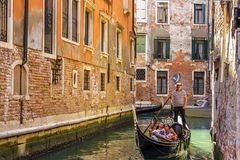 Venice, Italy - August 22, 2018: Gondola ruled by a gondolier in a narrow street canal of Venice.  royalty free stock image