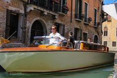 People in taxi boat on canal of Venice, Italy. Venice, Italy - August 13, 2016: People in taxi boat on famous Venetian canal Royalty Free Stock Photography