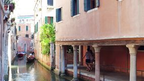 VENICE, ITALY - AUGUST 8, 2017. Young couple walking along Venetian canal with famous gondola Royalty Free Stock Photo