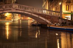 Venice Italy bridge and canal with boat at night. Long exposure at night on Venice canal with bridge and docked boat.  street lamps.  Reflection in water.  Stone Stock Photo