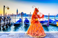 Venice, Italy - Carnival in Piazza San Marco. Venice, Italy - 9th February 2018: Carnival of Venice, beautiful mask at Piazza San Marco with gondolas and Grand royalty free stock images