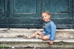Venice, Italy. A charming 4 year old girl in a blue dress plays in an old Venetian courtyard, sits on warm marble steps and laughs royalty free stock photo