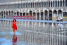 VENICE,ITALY dEmpty St Mark`s Square during a flood with beautiful water reflections of historical buildings on wet f. VENICE,ITALY 01.12.2018. Woman in red royalty free stock image