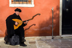 Street musician harp guitar Venice. VENICE, ITALY - FEB 7, 2013: Street musician playing a harp guitar on a street in Venice Stock Photo