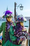 VENICE, ITALY - FEBRUARY 27, 2014: Carnival of Venice. Man and woman in masks and beautiful carnival costumes on background of Grand canal royalty free stock photo