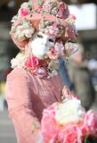 Venice, Italy - February 5, 2018: person in costume with carniva. Venice, Italy - February 5, 2018: carnival mask and a big bouquet of rose flower in hand Stock Photography